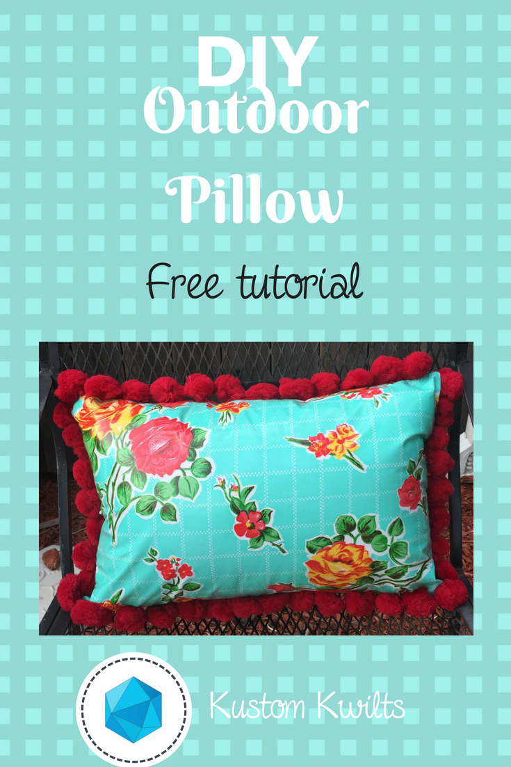 Oilcloth pillow with red pom pom trim