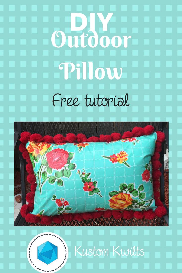 Oilcloth pillow with red pom pom trim