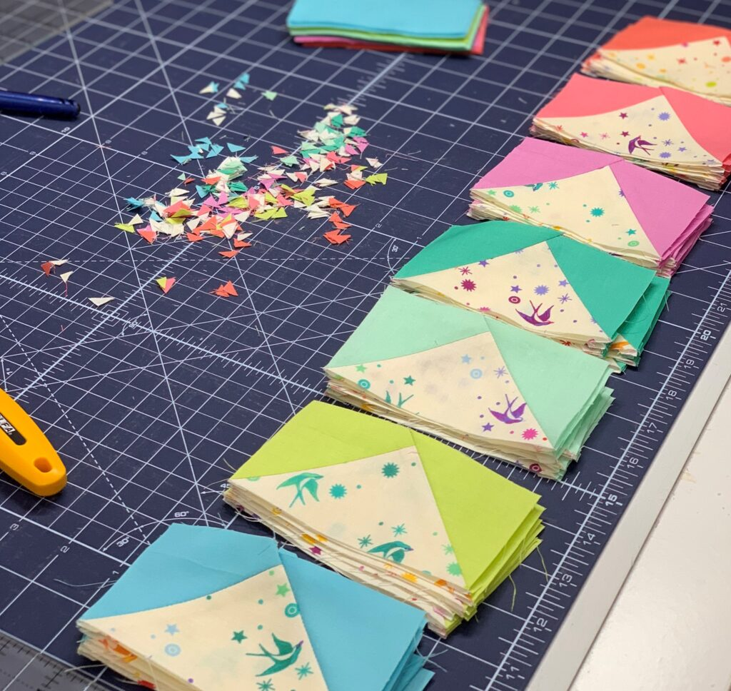 colorful flying geese lined up on a cutting mat with trimmings