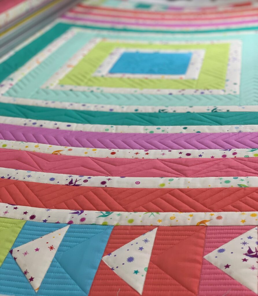 Detail of ruler work quilting on brightly colored cabin fever quilt