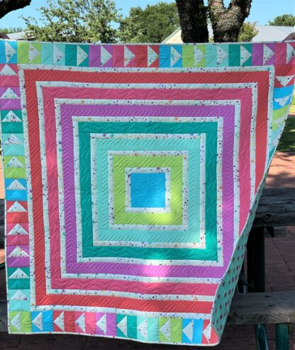 colorful log cabin quilt outside