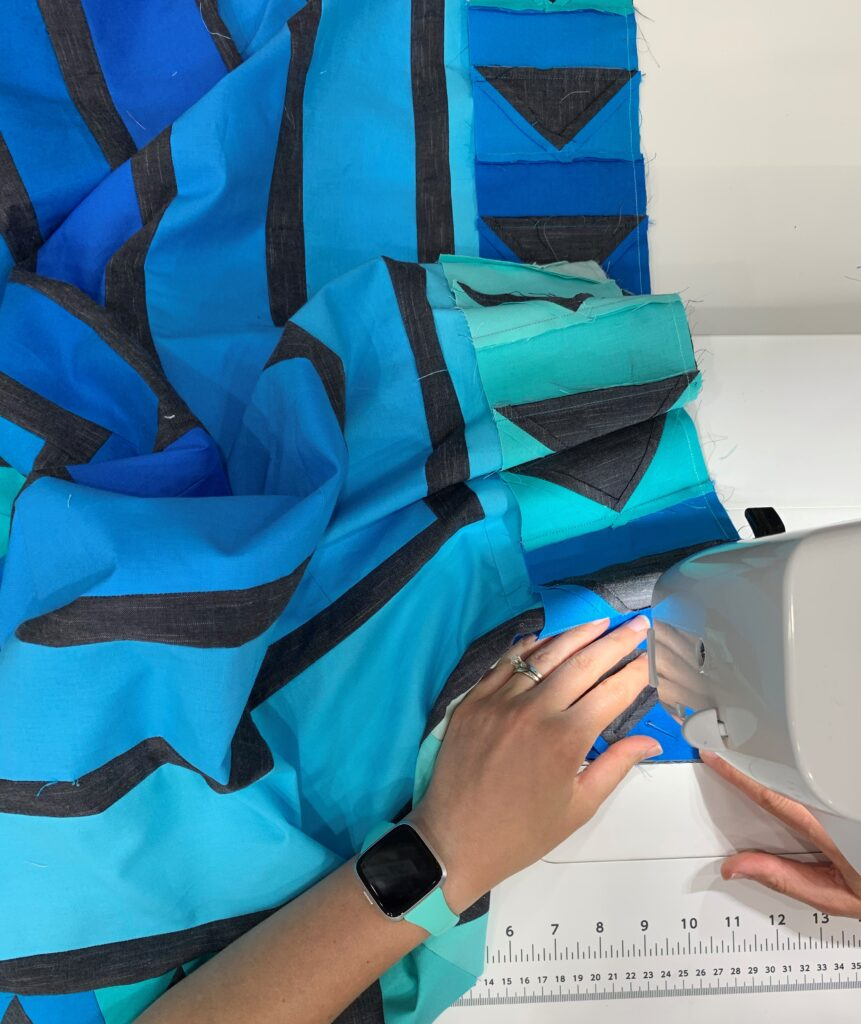 woman sewing together a blue version of the quilt at the sewing machine