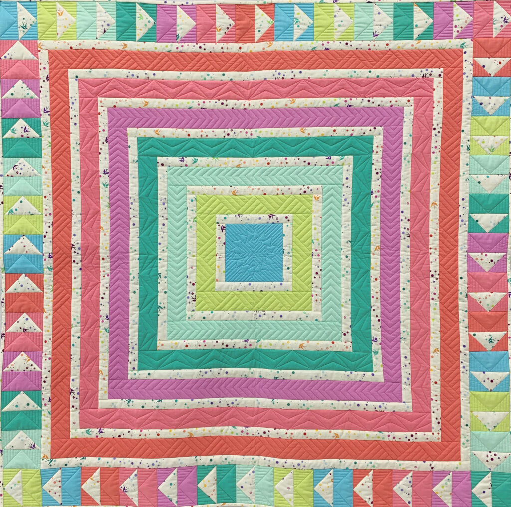 Cabin Fever quilt made from bright rainbow colors in log cabin style