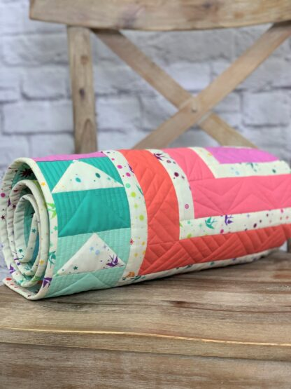 cabin fever baby quilt rolled up to show quilting detail
