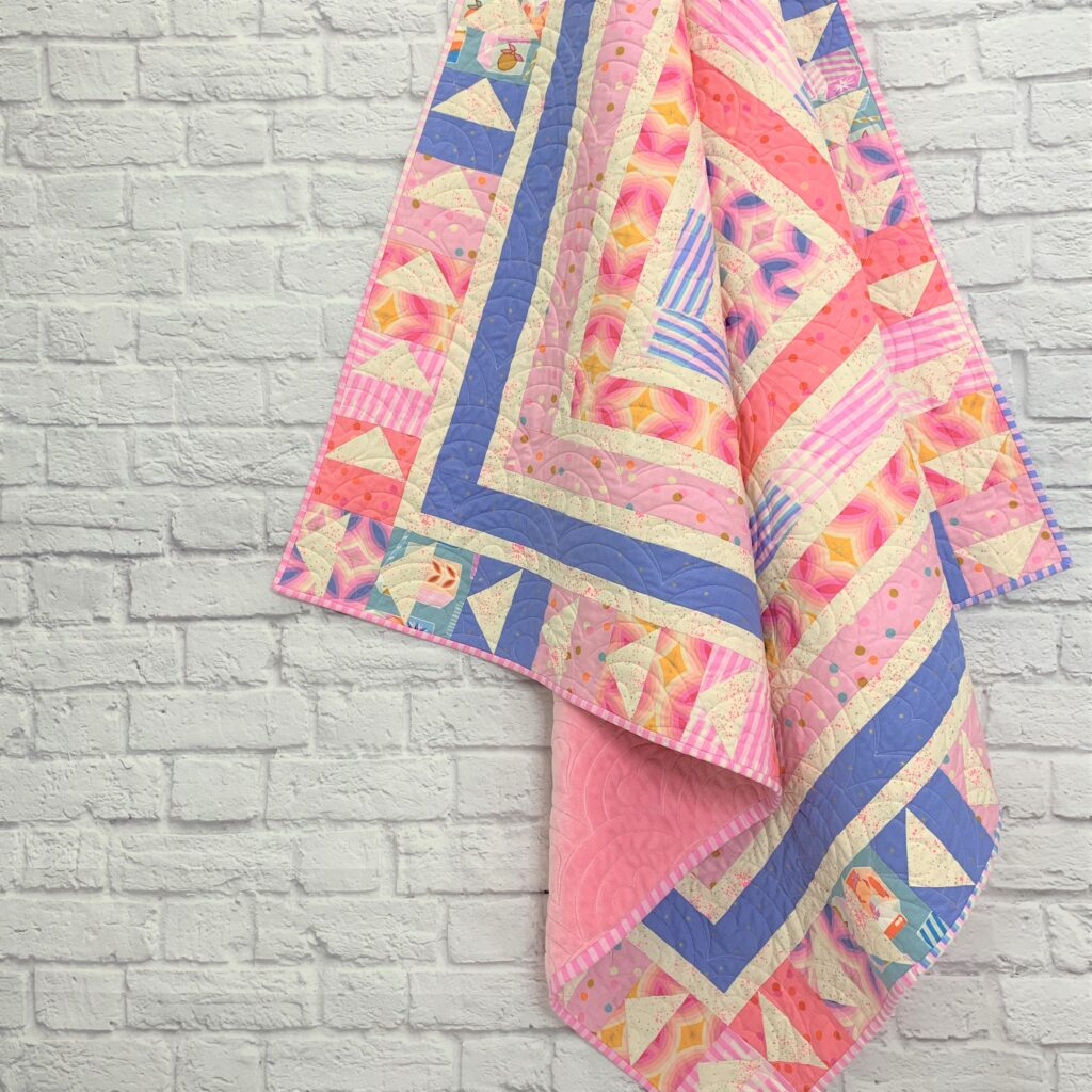 cabin fever quilt hanging from the top of he picture in pinks and blues