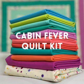 stack of colorful fabric for cabin fever quilt kit